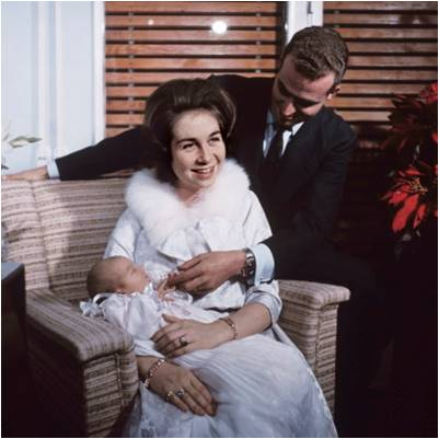 Queen Sofia holding Infanta Elena in 1963.