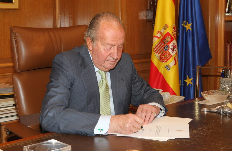 King Juan Carlos signing his abdication announcement.